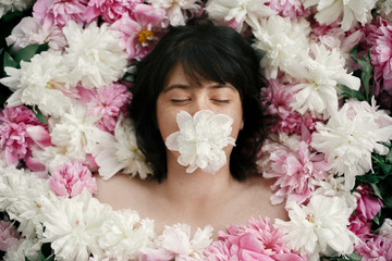 Portrait of boho woman with white peony in mouth lying in pink peonies. Creative art floral photo. Aroma and spa concept. International Womens Day. Beautiful brunette girl in many flowers