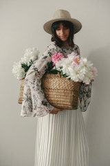 Blurred defocused image of boho girl holding pink and white peonies in rustic basket. Stylish hipster woman in hat and bohemian floral dress with flowers. International Womens Day