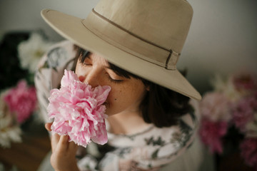 Portrait of boho girl smelling  pink peony at pink and white peonies on rustic wooden floor. Stylish hipster woman in bohemian dress  among flowers. International Womens Day