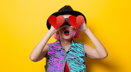 Portrait of young style hipster girl with pink hair style with binoculars with heart shape on yellow background