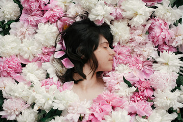 Beautiful brunette girl in many pink and white peonies. Happy boho woman portrait with peony flowers, top view. Creative floral photo. Aroma scent concept. International Womens Day