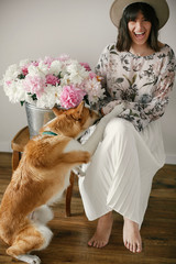 Stylish boho girl playing and smiling with cute golden dog at metal bucket with peonies on rustic wooden chair in home. Beautiful hipster woman having fun with her doggy. Friendship.