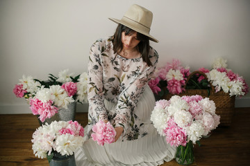Boho girl sitting at pink and white peonies in rustic basket and metal bucket on wooden floor. Stylish hipster woman in bohemian dress with flowers. Happy mothers day.