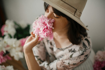 Portrait of boho girl smelling peony at pink and white peonies on rustic wooden floor. Stylish hipster woman in bohemian dress  among flowers. Aroma scent concept. Womens Day