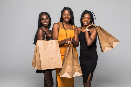 Portrait of three happy young african women wear in dresses holding shopping bags isolated over gray background
