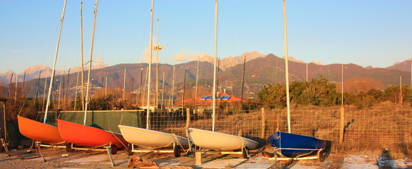 boats resting on the beach in their parking area waiting for the summer to set sail towards the blue sea