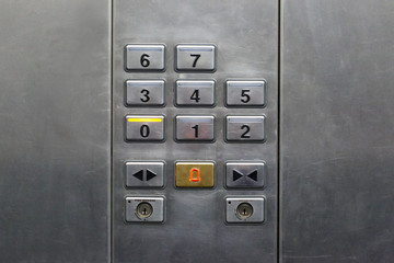 floor buttons on a gray steel wall in the elevator
