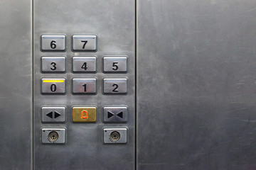floor buttons on a gray steel wall in the elevator, copy space