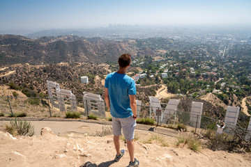 Young man sitting on the top of the Hollywood hills admiring LA downtown from behind the Hollywood sign.