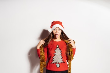 funny young girl showing tongue in red clothes waiting for new year and christmas