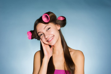 happy young girl going to a party, on her head big curlers