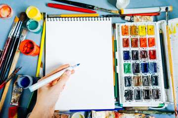 on a blue table are artistic supplies, paper, watercolors and gouache, many brushes