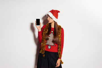 young girl in festive clothes is waiting for the new year and christmas is holding a smartphone
