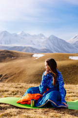 a young girl travels along the Caucasian ridge, enjoys the weather and clean air