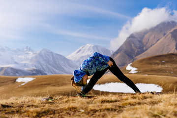 a young sports girl engaged in yoga in the Caucasus mountains, loves sports tourism