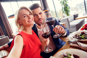 Young couple on date in restaurant sitting with glasses of red wine cheers taking selfie photos joyful