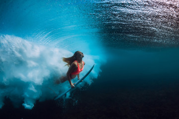 Attractive surfer woman dive underwater with big wave.
