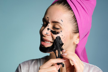 a smiling young girl in a pink towel removes a black cleansing mask from her face
