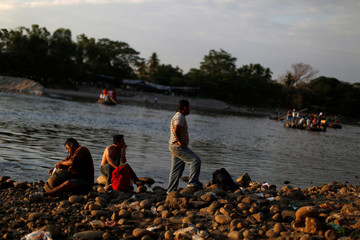 People belonging to a caravan of migrants from Honduras en route to the United States, rest by the Suchiate River in Tecun Uman