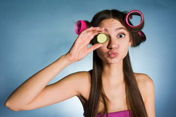 a funny young girl wants to look good, on the head of a curler, keeps a piece of cucumber for moisturizing the skin