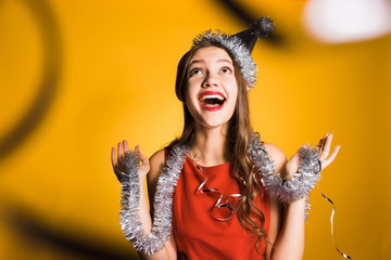 happy young girl with a silver tinsel around her neck celebrating the new year 2018
