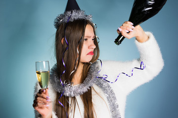 sad drunken girl holding a glass of champagne and an empty bottle, unhappy
