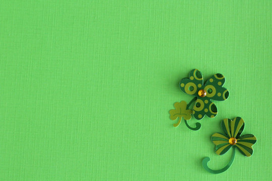 four leaf clovers laying flat on green background for St Patricks day with writing space