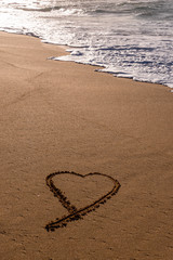 Heart drawn in the sand on the beach at sunset with waves washing in