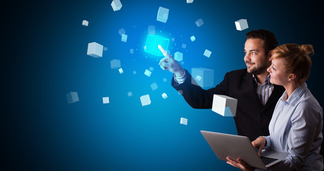 Man and woman touching hologram screen displaying cube symbols