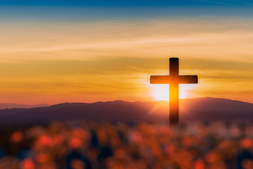 Silhouette of cross on mountain sunset background.