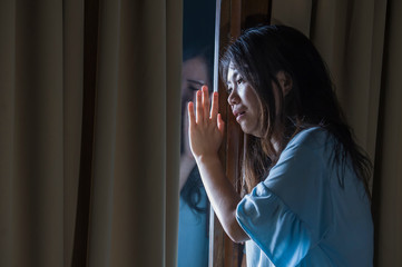 dramatic portrait of young sad and depressed Asian Japanese woman crying desperate broken heart suffering depression and anxiety in dark light at home curtains window