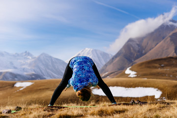 active girl is engaged in yoga and leads a healthy lifestyle, in nature, in the background of the Caucasus Mountains
