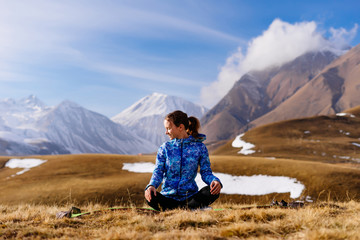 active girl does yoga and leads a healthy lifestyle, enjoys nature and the Caucasus Mountains, sits on the ground