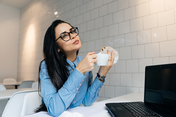 young business woman in glasses and blue shirt working on laptop in cafe and drinking delicious coffee
