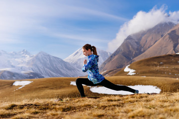 active young girl in a blue jacket is engaged in yoga, meditates against the background of the Caucasus mountains, enjoys nature