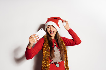 happy smiling girl in a hood like Santa Claus and New Year's clothes doing selfie