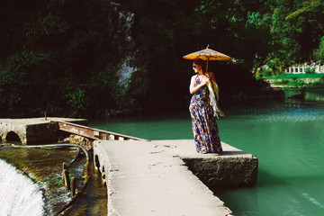 red-haired woman in a long dress walking through the park in Asia, holding a Chinese umbrella