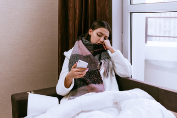 sad young girl is very sick, sore throat, neck warm scarf, holds smartphone in hand