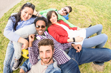 Multiracial best friends taking selfie at meadow picnic - Happy friendship fun concept with young people millenials having fun together outside on spring summer time - Neutral afternoon filter