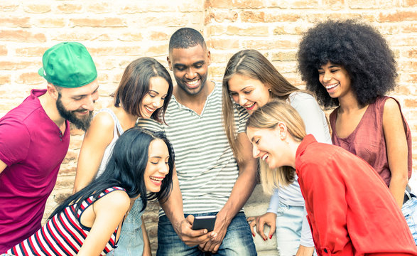 Millennials best friends using smart phone at city college backyard - Young people addicted by mobile smartphone - Technology and friendship concept sharing viral content on web - Bright vivid filter
