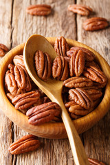 Raw pecan nuts in a bowl close-up. vertical