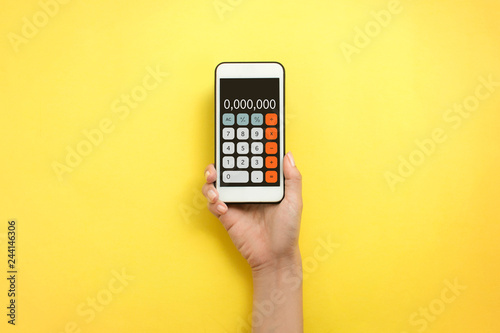 Flat lay hand holding mobile phone calculator on yellow
