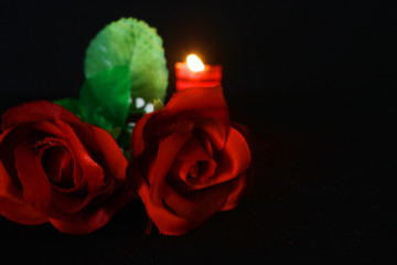 Photoshoot of red rose and candle burning on black background. Valentine day