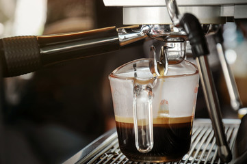 Fresh coffee in glass from professional coffee machine