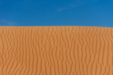 Contrast beautiful deep blue sky and orange rippled pattern sand dunes in the United Arab Emirates.