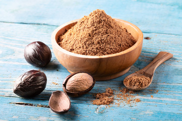 Fototapeta Whole inshell nut and nutmeg powder in a wooden bowl and spoon on old blue rustic background. obraz
