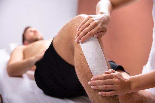 Therapist Waxing Man's Leg