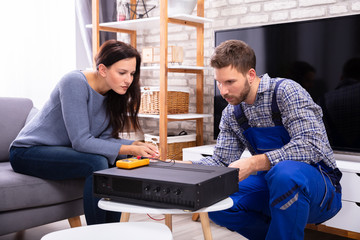 Woman Sitting Near Technician Repairing Amplifier