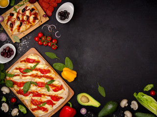 Delicious pizza with ingredients on black background.