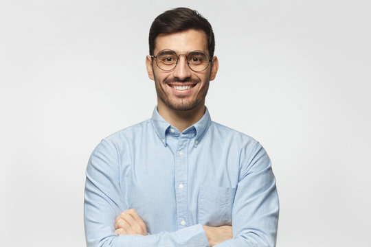 Portrait of young male teacher smiling, wearing blue shirt, isolated on gray background